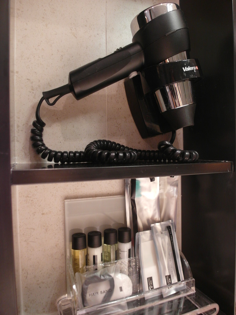 Well-equipped bathroom with hair dryer and amenities