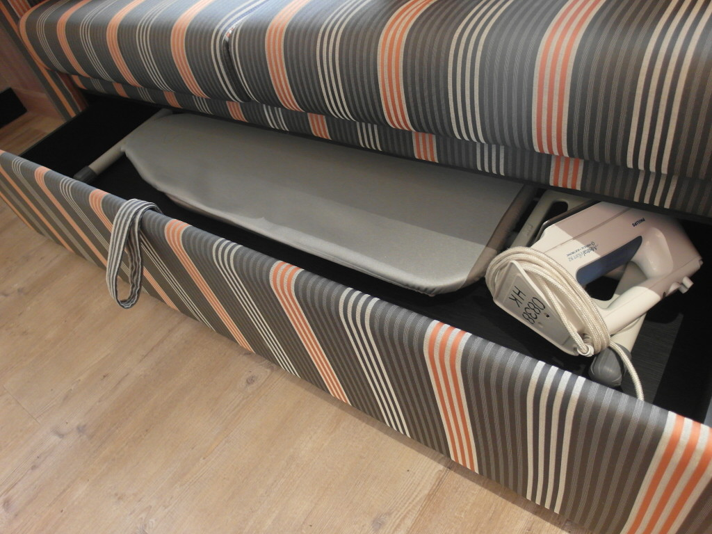 Ironing board and iron neatly stowed away beneath the sofa