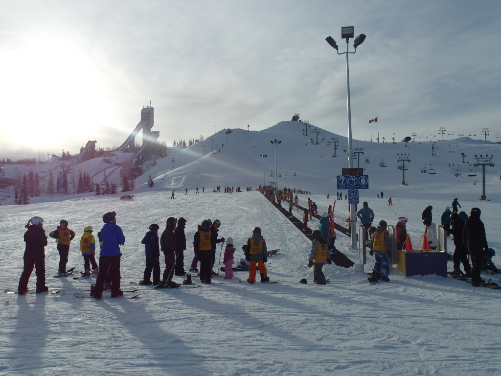 Many many young kids learning how to ski and snowboard.